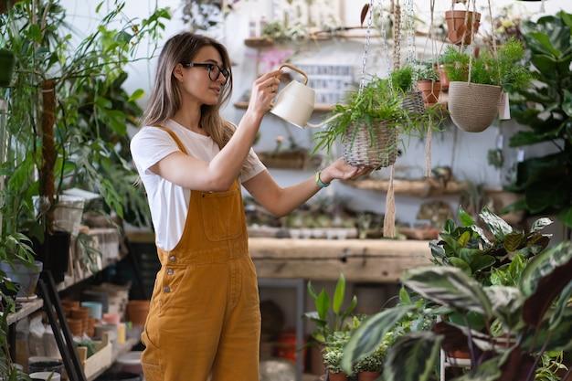 Jardinero de mujer regando la planta de interior en macetas en invernadero, utilizando una regadera de metal