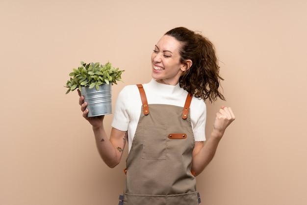 Jardinero mujer sosteniendo una planta celebrando una victoria