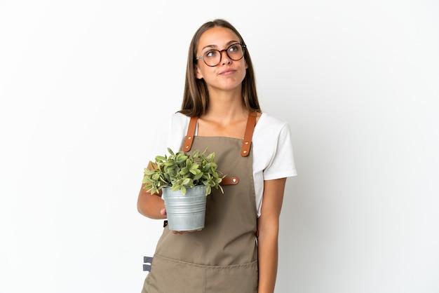 Jardinero niña sosteniendo una planta sobre fondo blanco aislado y mirando hacia arriba