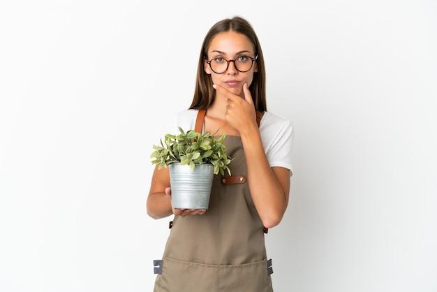 Jardinero niña sosteniendo una planta sobre fondo blanco aislado pensando