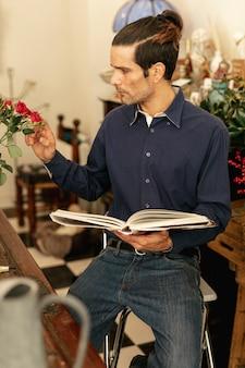 Jardinero sentado con un libro en sus manos.