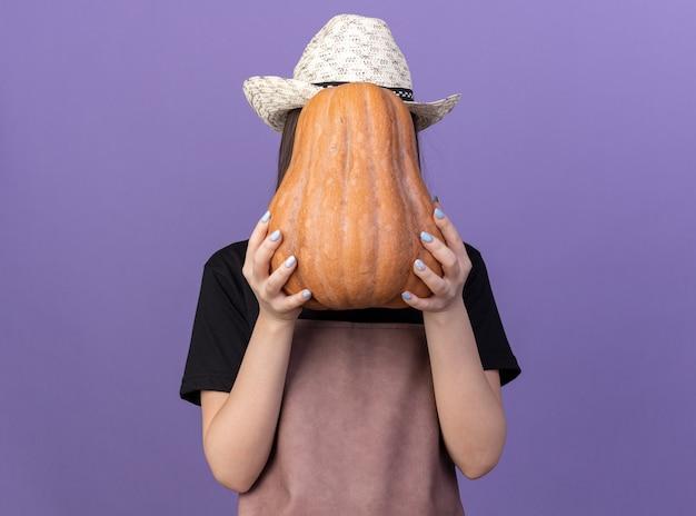 Jardinero de sexo femenino bastante caucásico con sombrero de jardinería sosteniendo calabaza delante de la cara
