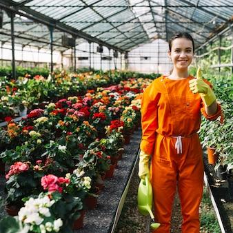 Jardinero de sexo femenino joven feliz con la regadera que gesticula los pulgares para arriba