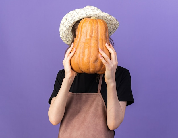 Jardinero de sexo femenino joven con sombrero de jardinería rostro cubierto con calabaza