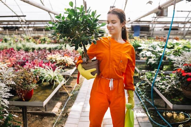 Jardinero de sexo femenino joven sonriente que sostiene la planta y la regadera en conserva