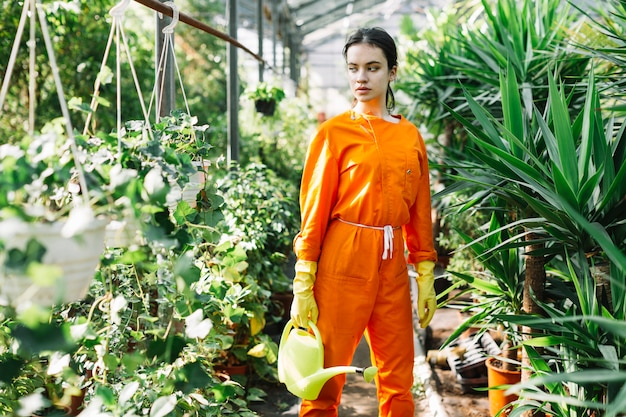 Jardinero de sexo femenino con la regadera que mira las plantas en maceta