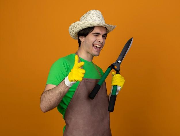 Jardinero de sexo masculino joven parpadeó en uniforme con sombrero de jardinería con guantes sosteniendo tijeras mostrando gesto