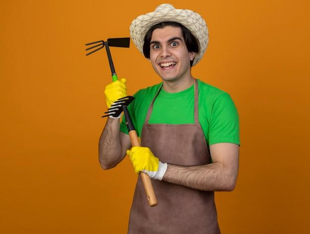 Jardinero de sexo masculino joven sonriente en uniforme que lleva el sombrero de jardinería con los guantes que sostienen el rastrillo de la azada con el rastrillo aislado en la pared naranja