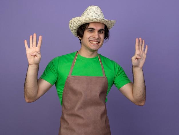 Jardinero de sexo masculino joven sonriente en uniforme que lleva el sombrero que cultiva un huerto que muestra cuatro aislados en púrpura