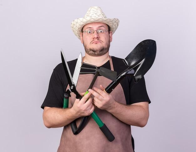 Jardinero de sexo masculino joven sorprendido con sombrero de jardinería sosteniendo la pala con tijeras y rastrillo de azada aislado en la pared blanca