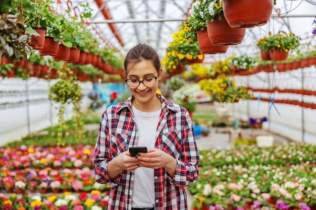 Jardinero sonriente de pie en invernadero y tomando pedidos de un cliente a través de un teléfono inteligente.