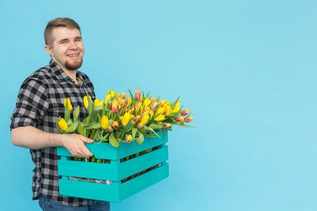 Jardinero varón caucásico con caja de tulipanes riendo en la pared azul con espacio de copia