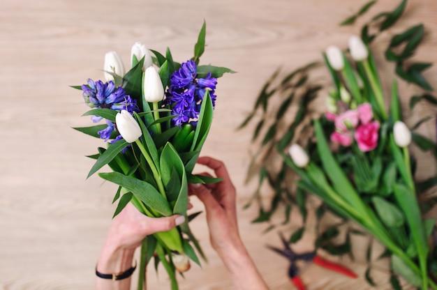 Los jardineros en la florería hacen un ramo. tienda de flores de estilo de vida. hermosa composición de flores. detalle.