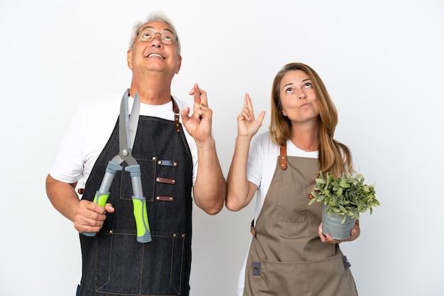 Jardineros de mediana edad sosteniendo una planta y tijeras aisladas sobre fondo blanco con los dedos cruzando y deseando lo mejor