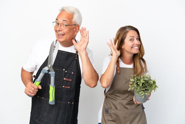 Jardineros de mediana edad sosteniendo una planta y tijeras aisladas sobre fondo blanco escuchando algo poniendo la mano en la oreja