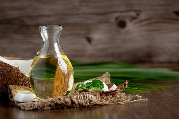 Jarra de aceite de coco con coco sobre fondo oscuro