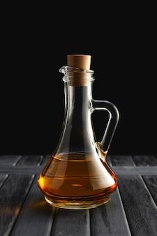 Jarra con aceite en mesa de madera