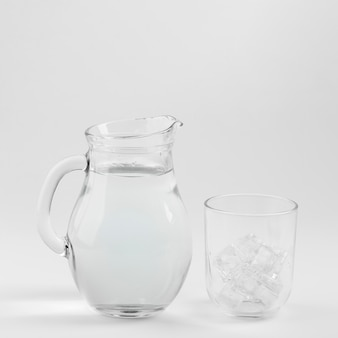 Jarra de agua y vaso lleno de hielo