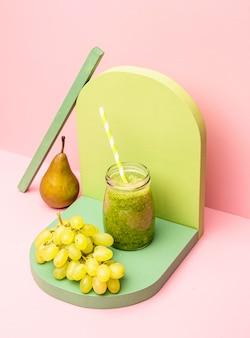 Jarra con batido fresco de pera y uvas en el escritorio