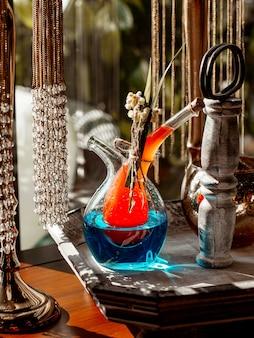 Jarra de bebidas única con dos partes llenas de cócteles naranjas y azules