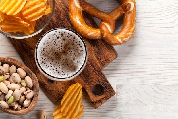 Jarra de cerveza y aperitivos en mesa de madera.