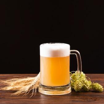 Jarra de cerveza con cebada y lúpulo sobre tabla de madera