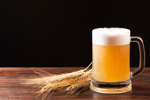 Jarra de cerveza y cebada sobre tabla de madera