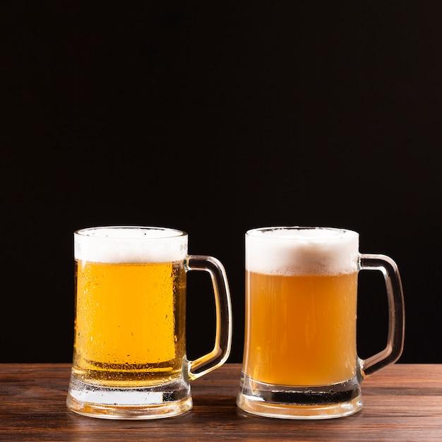 Jarra de cerveza con espuma sobre tabla de madera