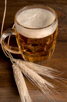 Jarra de cerveza fresca con cebada de espiga en mesa de madera