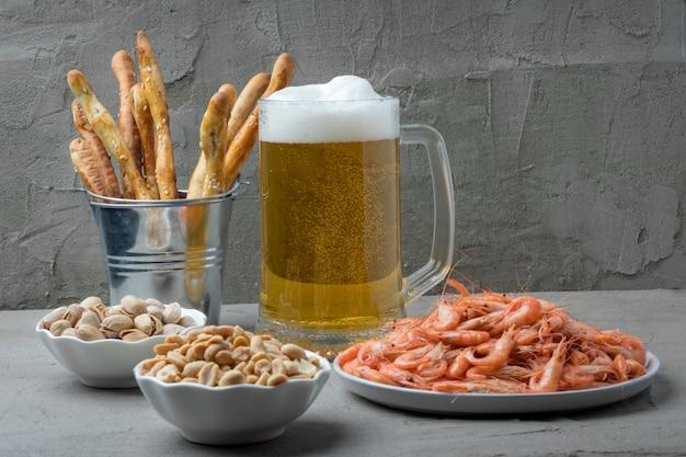 Jarra de cerveza fresca y sabrosos aperitivos en mesa gris