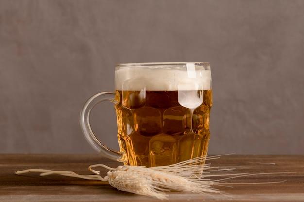 Jarra de cerveza light con trigo en mesa de madera