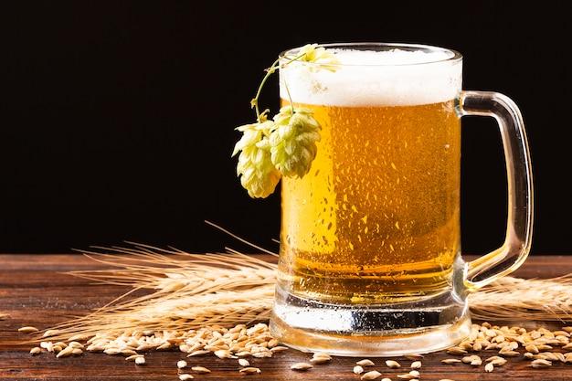 Jarra de cerveza con lúpulo sobre tabla de madera