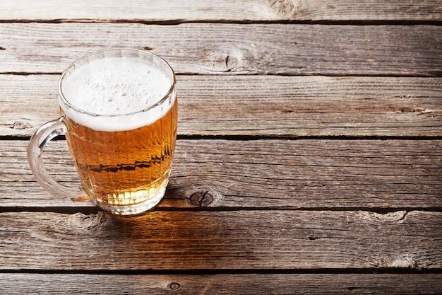 Jarra de cerveza en mesa de madera