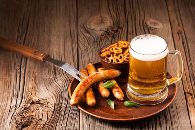 Jarra de cerveza con salchichas y aperitivos en tablero de madera