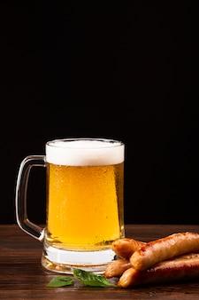 Jarra de cerveza y salchichas en tablero de madera