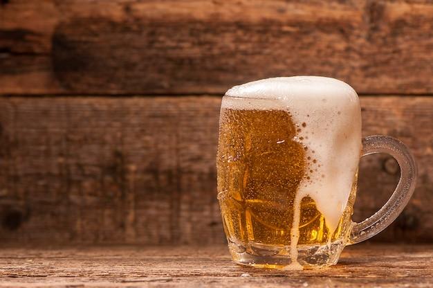 Jarra de cerveza sobre fondo de madera