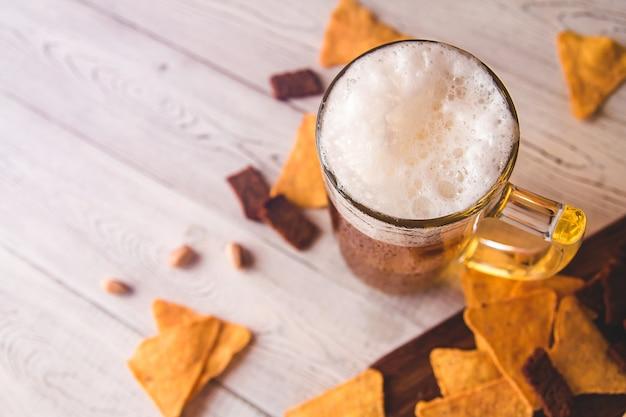 Jarra de cerveza de vidrio y bocadillos de cerveza en madera, vista superior
