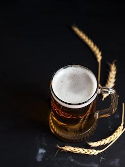 Jarra de cerveza de vidrio sobre una mesa oscura