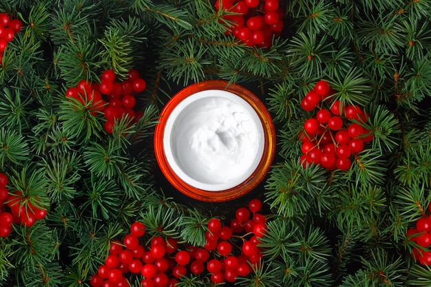 Jarra con crema facial hidratante en el fondo de ramas de abeto, coníferas y bayas de viburnum. cosmética natural de invierno para el cuidado de la piel.