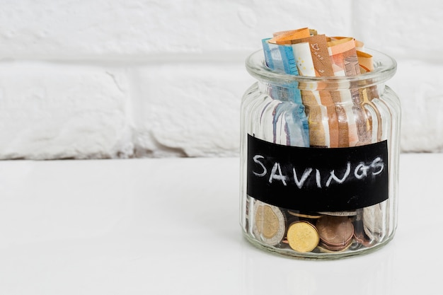 Jarra de vidrio de ahorro con billetes y monedas en euros