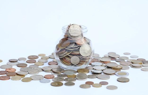 Jarra desbordante de monedas internacionales sobre fondo blanco