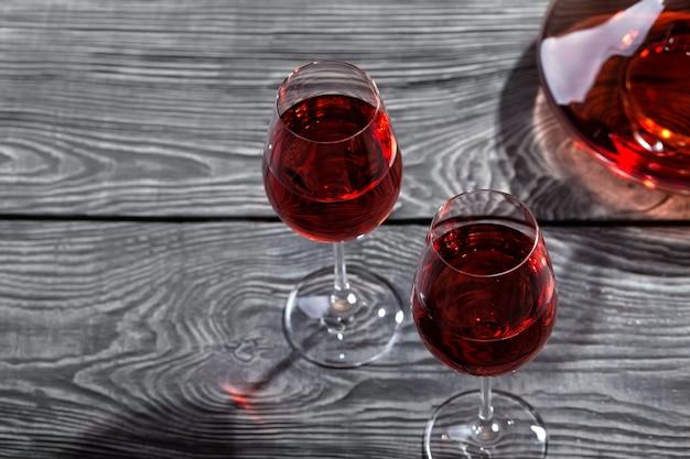 Jarra y dos copas de vino tinto en una mesa de madera