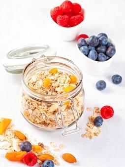 Jarra con granola casera con nueces, frutas secas y bayas frescas.