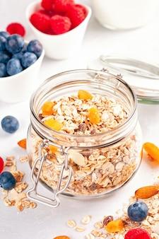 Jarra con granola casera o muesli de avena con nueces, frutas secas y bayas frescas.