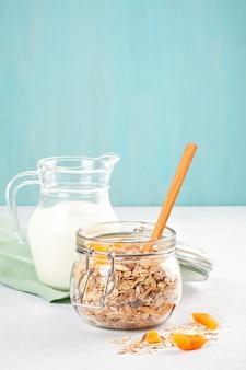 Jarra con granola casera o muesli de avena con nueces y frutas secas y leche.