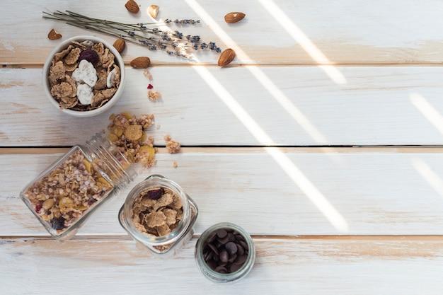 Jarra de granola derramada cerca de copos de maíz; frutas secas y chips de chocolate sobre tabla de madera.