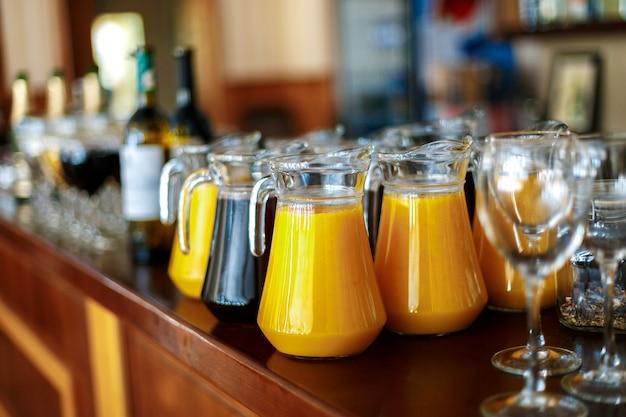 Una jarra de jugo fresco de naranja y uvas en la barra