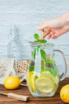 Jarra de jugo de limón con cuchillo de madera, limones, mano sujetando hojas vista lateral sobre una superficie blanca y de madera