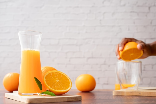 Jarra de jugo de naranja recién exprimido con mano humana exprimiendo naranja, sin azúcar agregada.