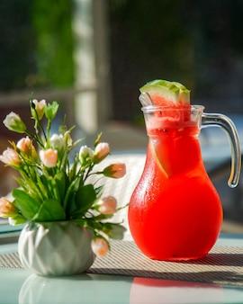 Jarra con jugo de sandía fría y un jarrón con flores.